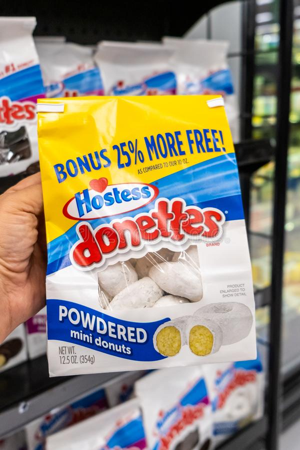 Shoppers hand holding a Package of Hostess brand donetttes powered mini donuts stock images