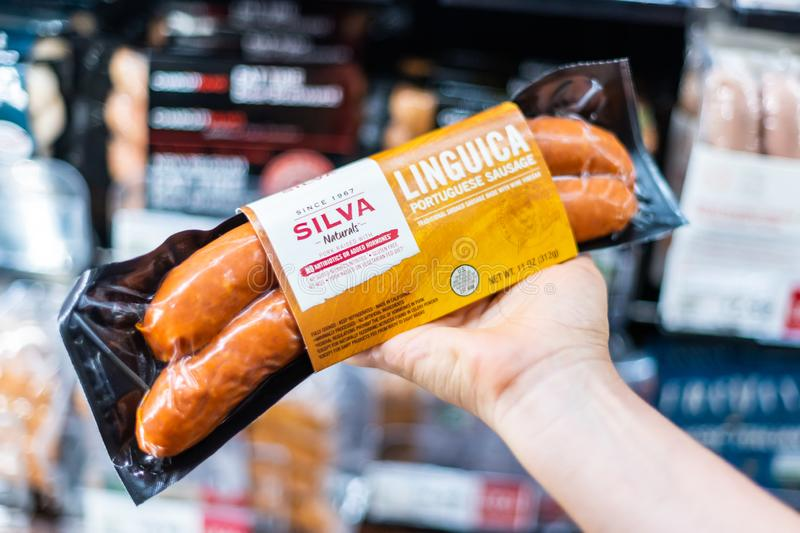 Shoppers hand holding a package of SILVA brand portuguese linguica sausage. In a supermarket aisle royalty free stock image