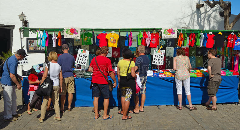 Shoppers looking at T-shirt on market stall. stock photography