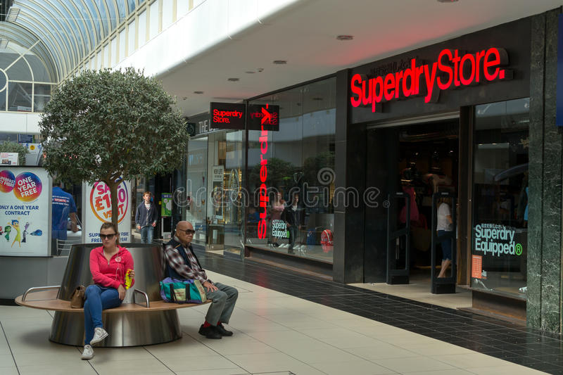 Shoppers shopping in Chelmsford England. 01/09 - Shoppers sit and rest on public seating in a Chelmsford shopping centre during the summer of 2015 in England stock images
