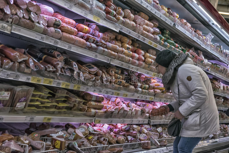Shoppers in a supermarket in the sausage department. St. Petersburg, Russia stock image