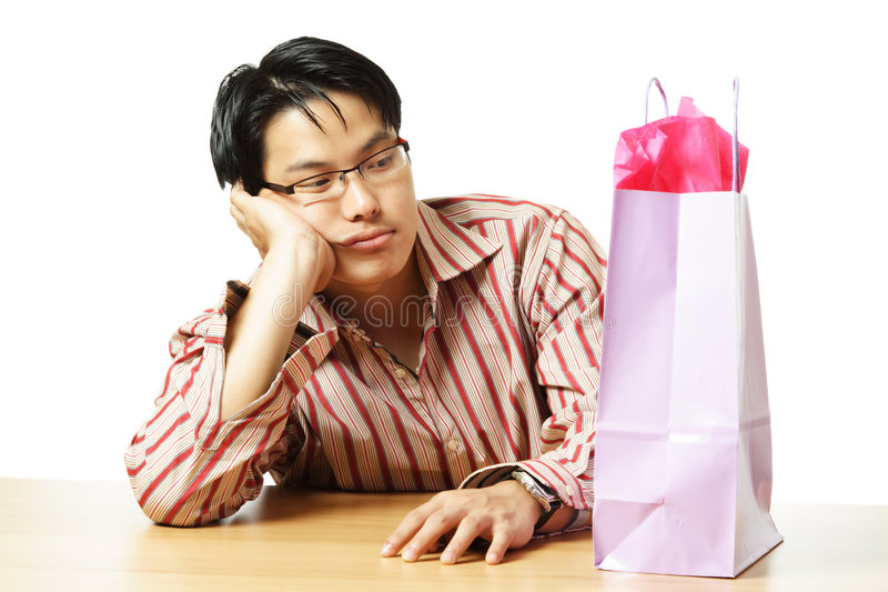 Shopping. An isolated shot of a sad young man with a shopping bag royalty free stock images
