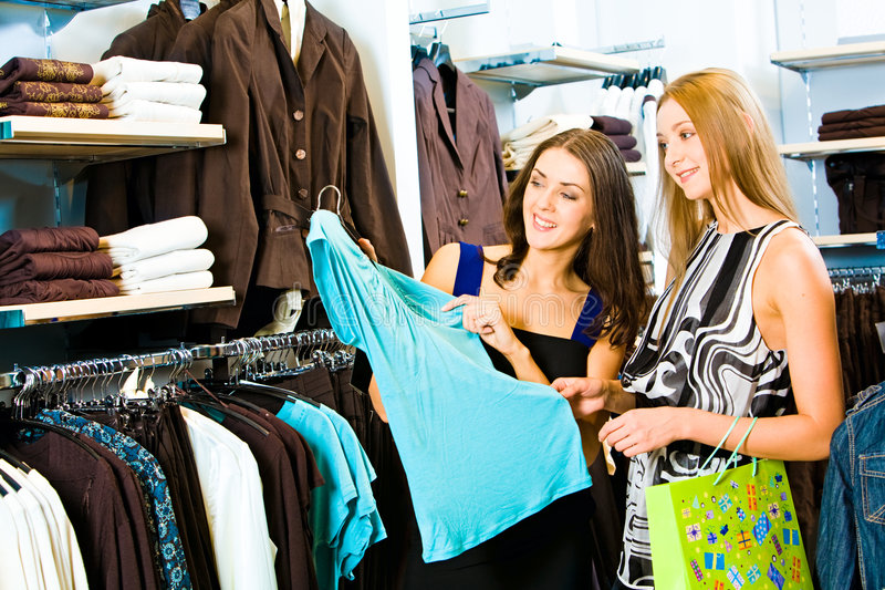 Shopping. Photo of two girls in the clothing store holding a blue dress and looking at it with smiles on the background of different clothes stock photo