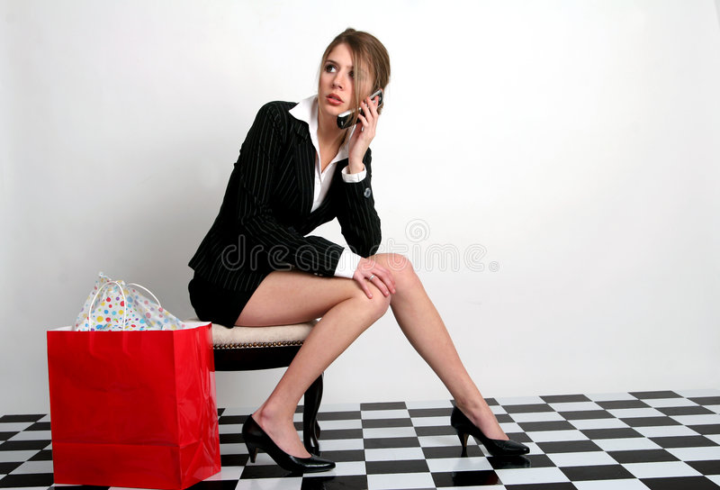 Shopping. Young woman talking on the cellphone while sitting with a red shopping bag next to her royalty free stock photography