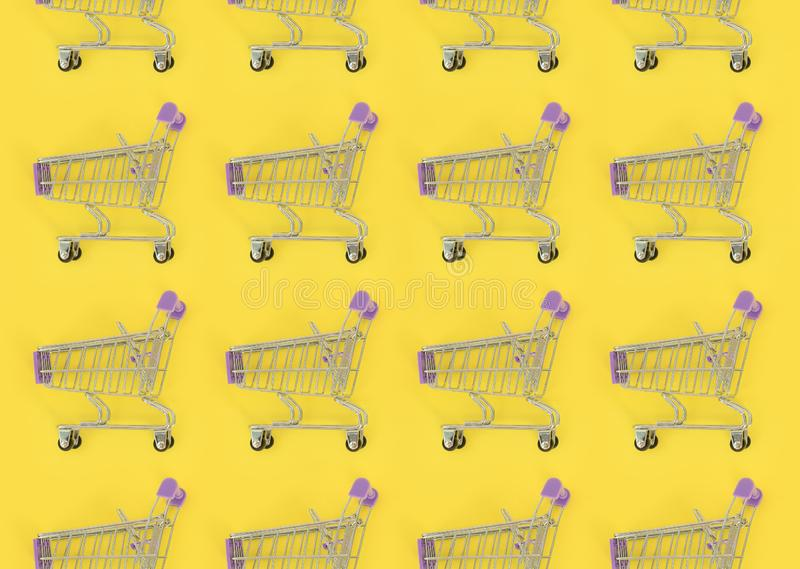 Shopping addiction, shopping lover or shopaholic concept. Many small empty shopping carts perform a pattern on a pastel colored stock photo