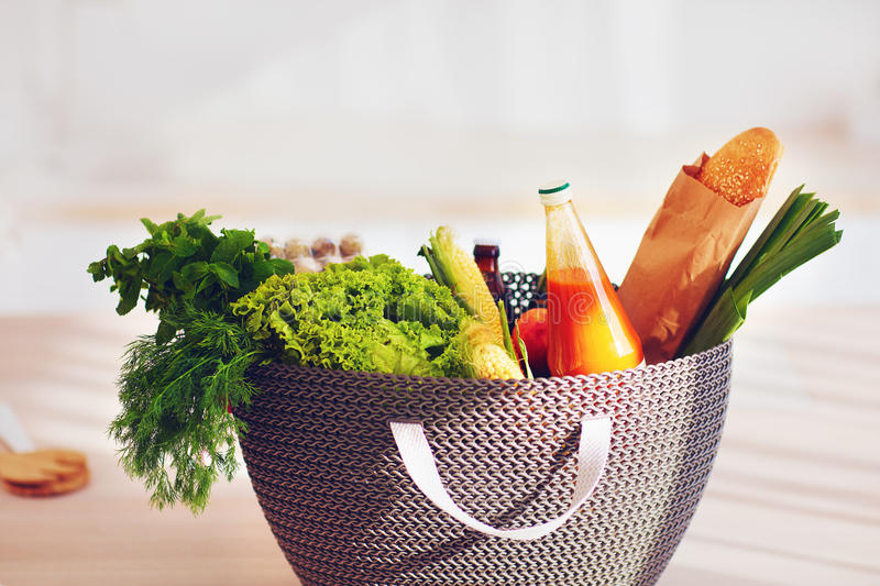 Shopping bag full of fresh food on kitchen desk. Big shopping bag full of fresh food on kitchen desk stock photography