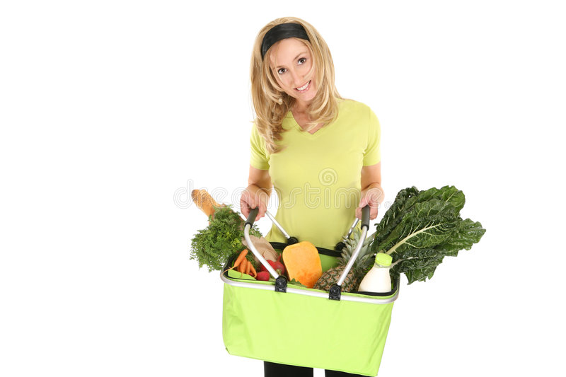 Shopping bag full of groceries. A girl holding an eco shopping bag holding a selection of milk, eggs, bread, fruit and vegetables stock image