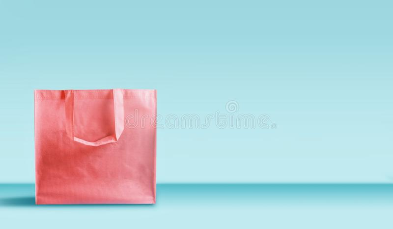 Shopping bag in living coral color standing on table at turquoise wall background. Branding mock up. Copy space. Purchase , sale. And promotion concept. Banner stock photo