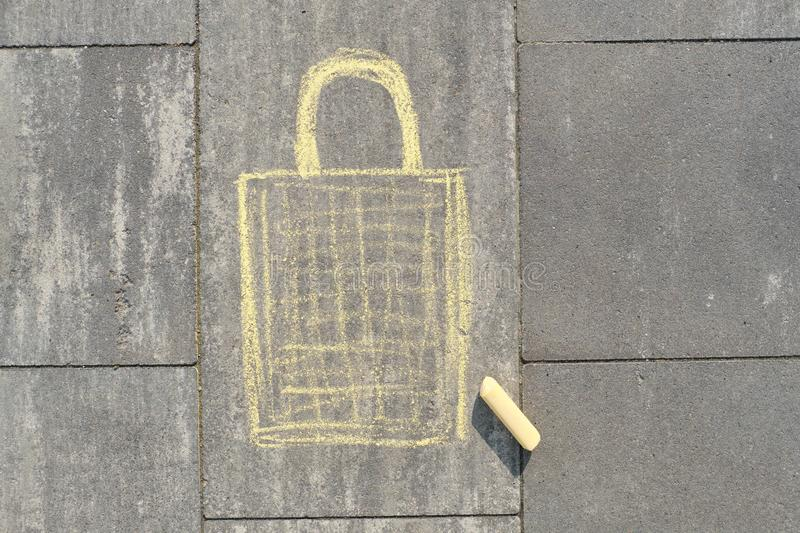 Shopping bag picture written on gray sidewalk in crayons royalty free stock photos