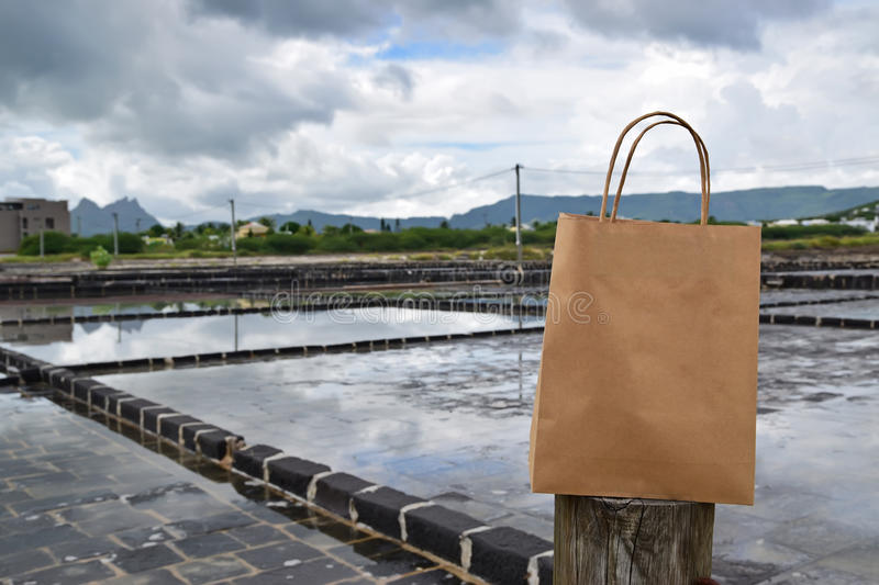 Shopping bag with salt pans in the background. This image can be used to show people do shop for artisan salt made by niche specialty salt maker who claims to stock photo