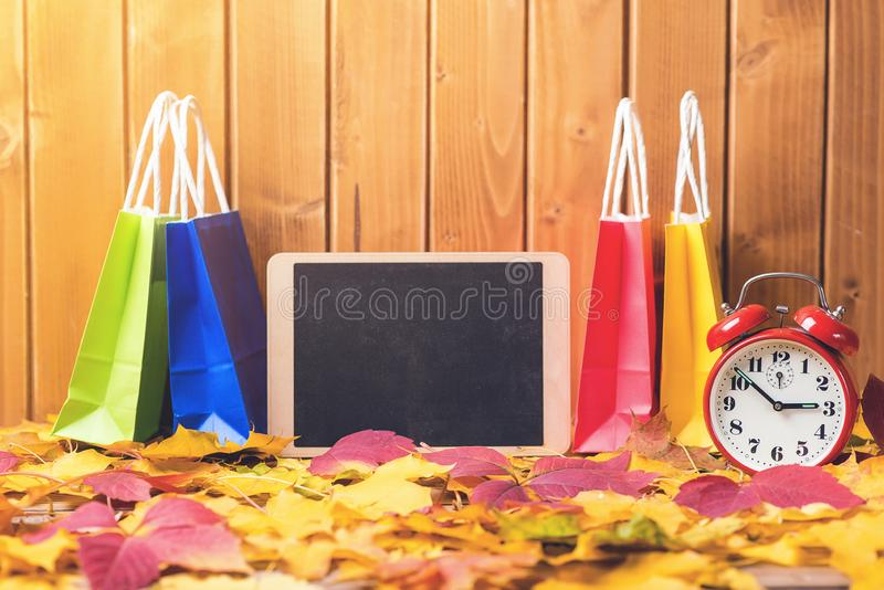 Shopping bags on autumn leaves background. Chalkboard and fallen leaves. Autumn sales. Black friday concept. Autumn shopping time. royalty free stock images