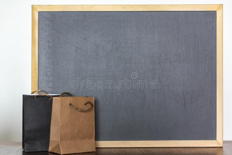 Shopping bags and blackboard on the background with copy space. Commercial business, shopping, retail sale concept. Shopping bags and blackboard on the royalty free stock images