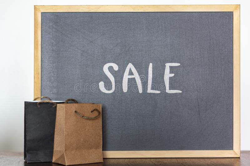 Shopping bags and blackboard on the background with the word Sale. Sale, discount, season sales concept stock photography