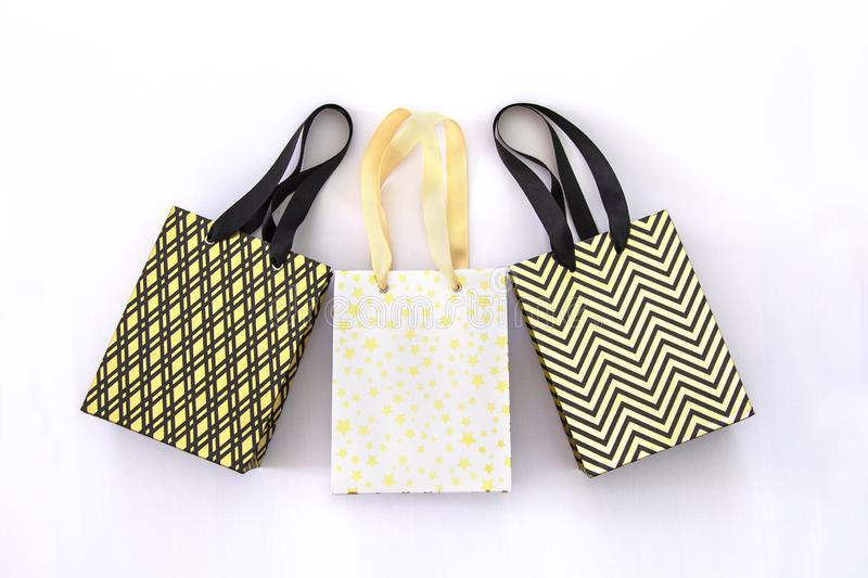 Shopping bags, gift boxes in modern style on white background. Golden stars, black geometric lines- fashion modern design. Minimal stock photos