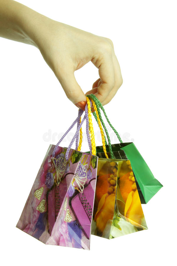 Shopping bags in hand, isolated. The girl is holding three bags of shopping royalty free stock images