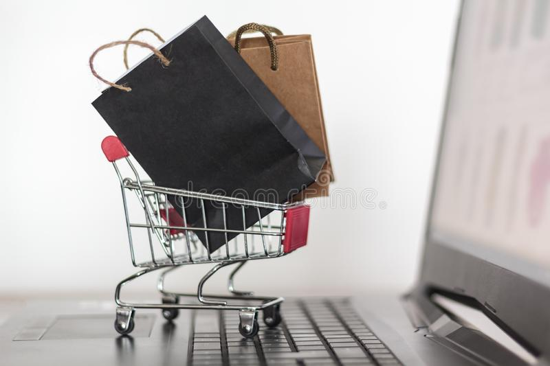 Shopping bags and trolley on laptop keyboard. Online shopping, e-commerce concept stock photo