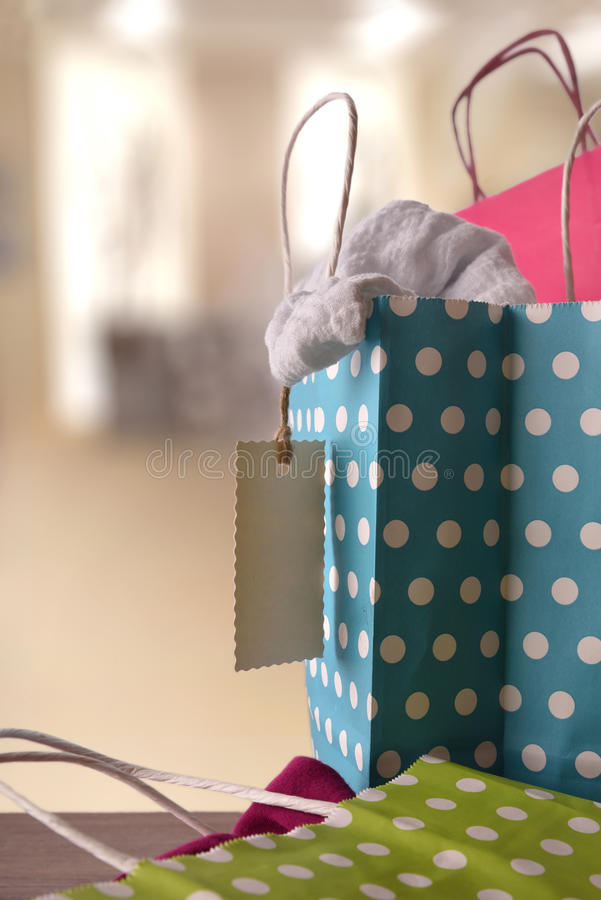 Shopping bags with new clothes inside in a shop vertical royalty free stock photography