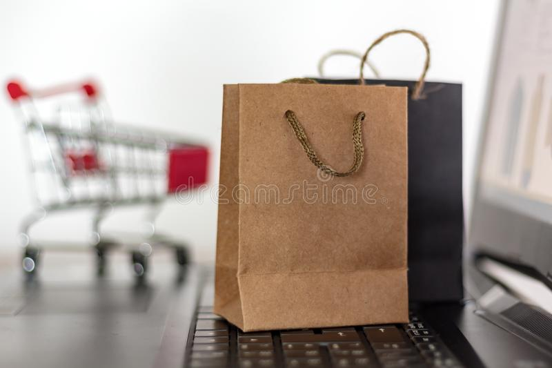 Shopping bags and trolley on laptop keyboard. Online shopping, e-commerce concept royalty free stock photography