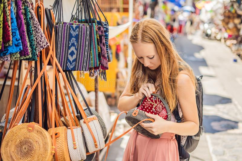 Shopping on Bali. Young woman chooses Famous Balinese rattan eco bags in a local souvenir market in Bali, Indonesia stock images