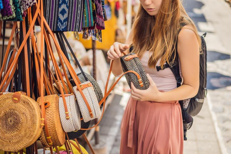 Shopping on Bali. Young woman chooses Famous Balinese rattan eco bags in a local souvenir market in Bali, Indonesia stock photo