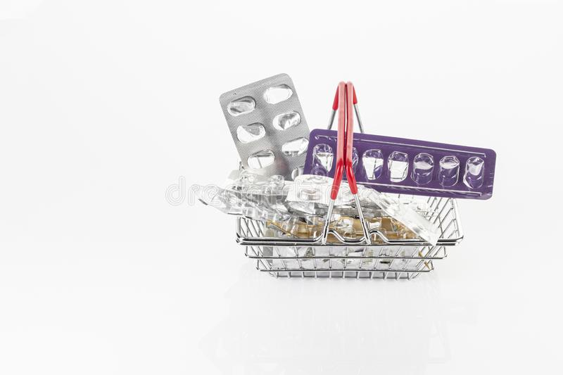 Shopping basket filled with empty pill packs and isolated medication on a white background. Recycling concept stock photography