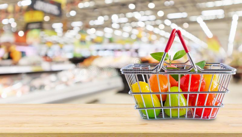 Shopping basket with fruits on wood table over grocery store. Supermarket blur background royalty free stock images