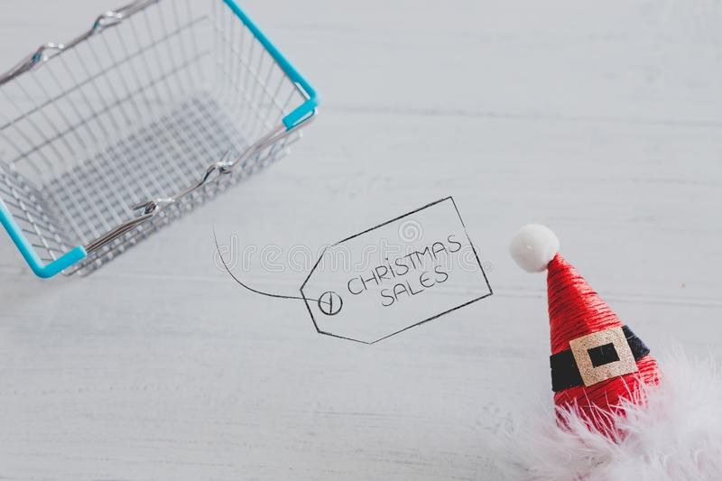 Shopping basket with santa claus hat and sales price ttag design. Christmas shopping concept: shopping basket with santa claus hat and sales price ttag design stock photo