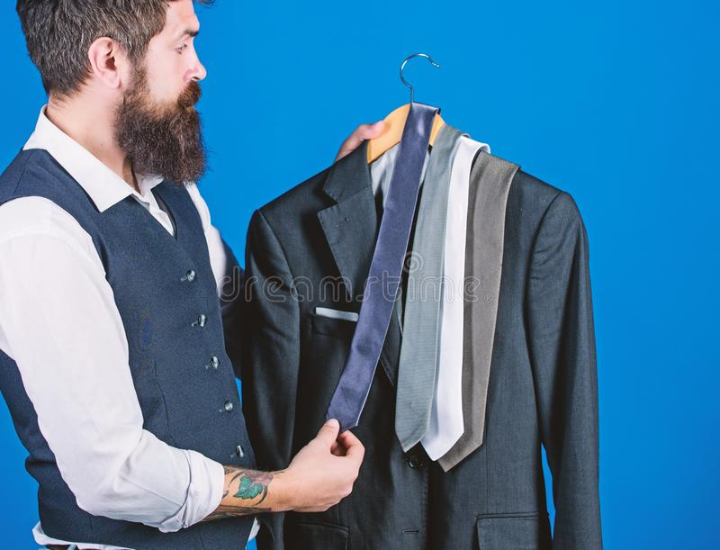 Shopping for business attire. Bearded shopper matching necktie to coat in shopping mall. Hipster shopping the latest tie stock photography