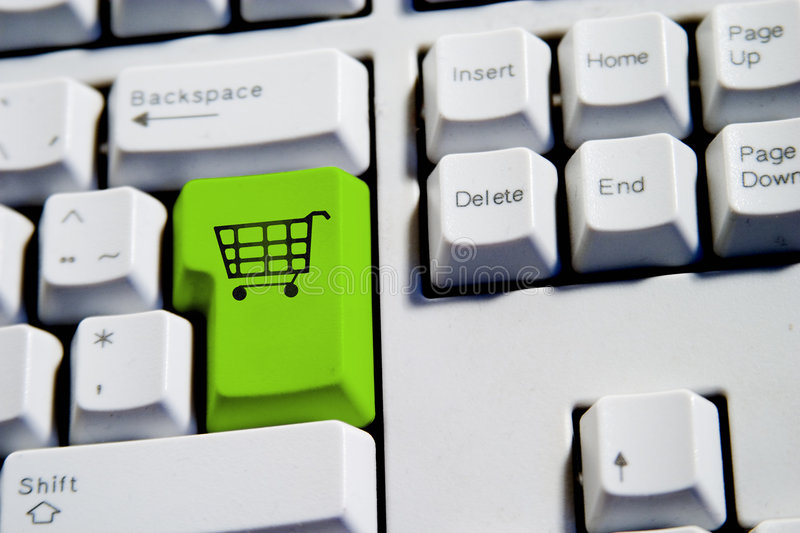 Shopping Cart. Computer Keyboard from a desktop computer with the enter key highlighted in green with a large shopping cart on it