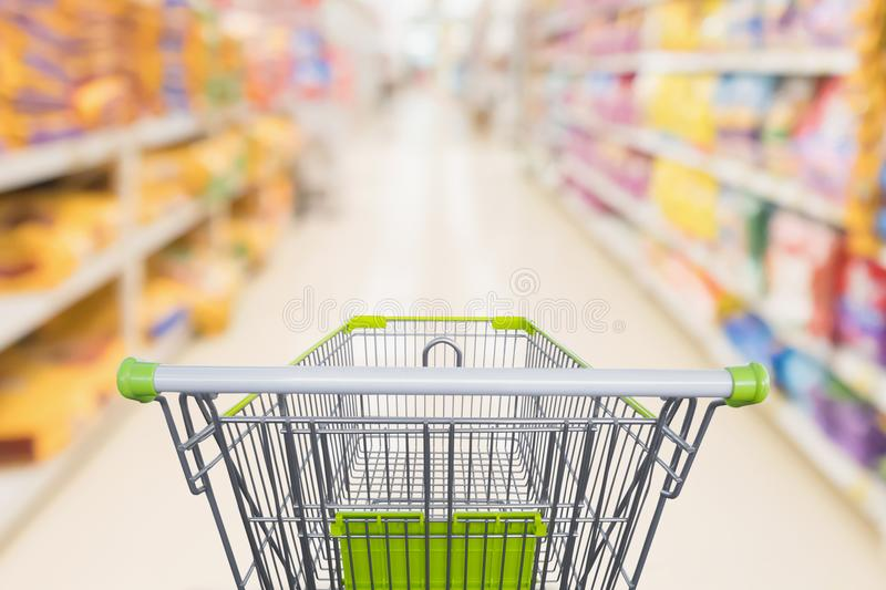Shopping cart with abstract blur supermarket discount store. Aisle and pet food product shelves interior defocused background stock photos