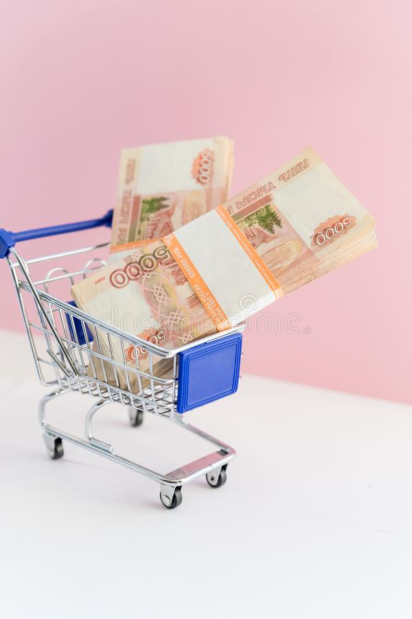 Shopping cart with banknotes on pink background. financial concept.online shopping concept. Multi-currency basket royalty free stock photo