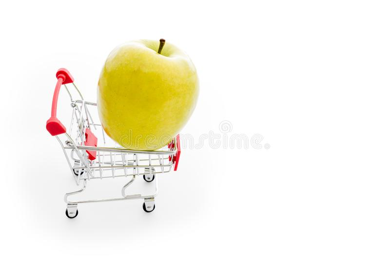 Shopping cart with big green apple on white. Buying fruits from supermarket. Self-service supermarket full shopping stock photography