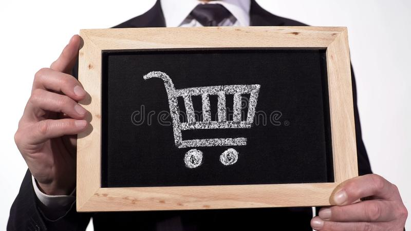 Shopping cart on blackboard in businessman hands, retail trade, consumer bundle. Stock footage royalty free stock photography