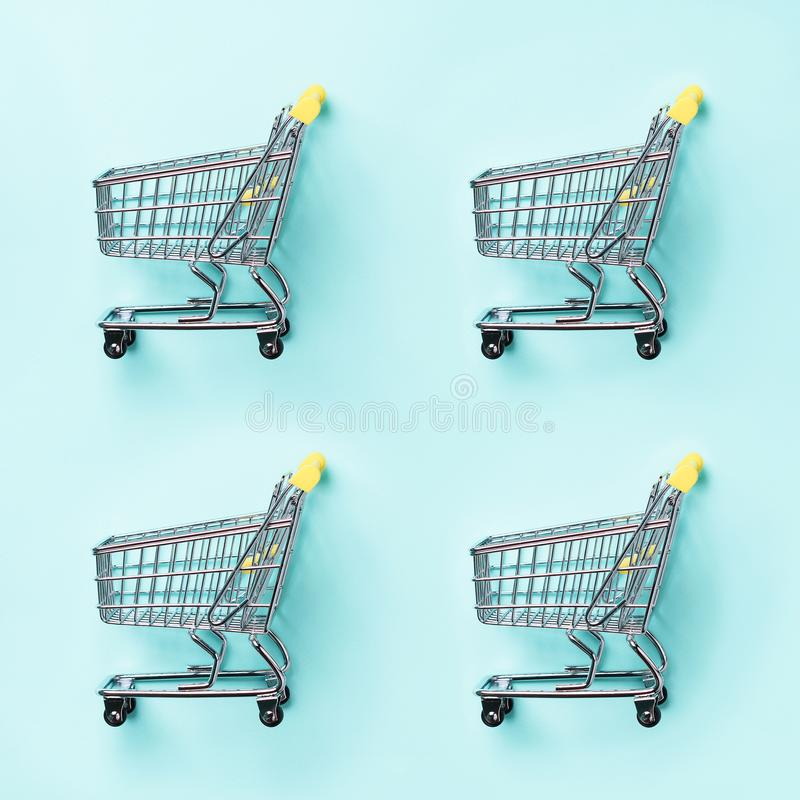 Shopping cart on blue background. Minimalism style. Creative design. Top view with copy space. Shop trolley at supermarket. Sale,. Discount, shopaholism concept royalty free stock photography