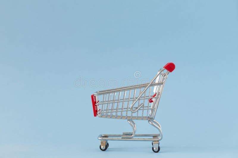 Shopping cart on blue background. Minimalist style. Creative design. Copy space. Sale, discount, shopaholism concept. Selective focus stock photography