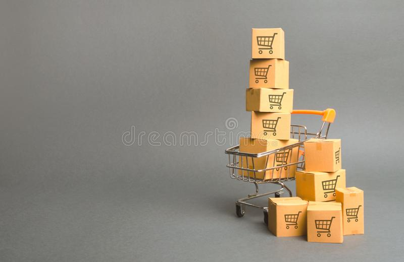 Shopping cart and boxes with drawing of smaller carts. goods sale. commerce, online shopping. Purchasing power, delivery order. E-commerce, sales and sale of stock photography
