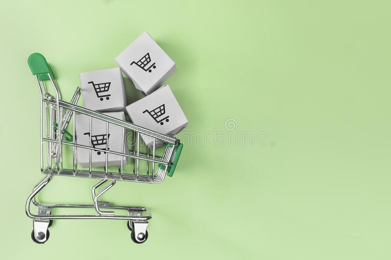 Shopping cart with boxes on green background. The concept of delivering and online shopping royalty free stock photography