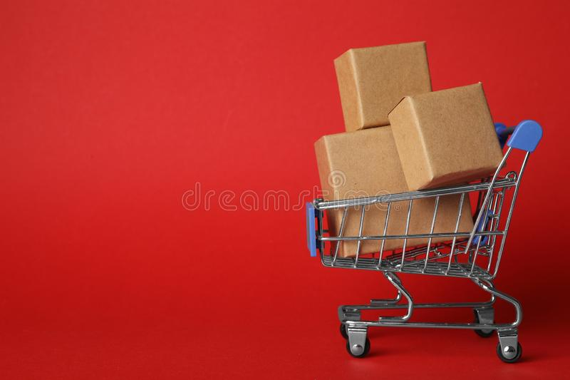 Shopping cart with boxes on red background. Logistics and wholesale concept. Shopping cart with boxes on red background, space for text. Logistics and wholesale royalty free stock photos