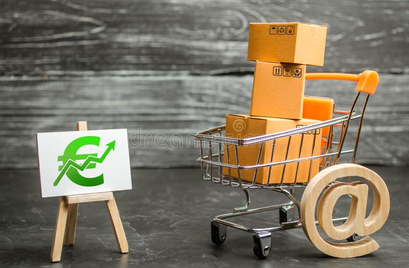 A shopping cart with boxes symbolizing internet trading and a stand with a green Euro up arrow. shopping online. sales of goods. And services. Internet network stock photos