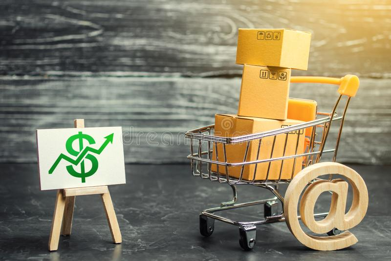 A shopping cart with boxes symbolizing internet trading and a stand with a green up arrow. shopping online. Internet network trade. Advertising services. E royalty free stock image
