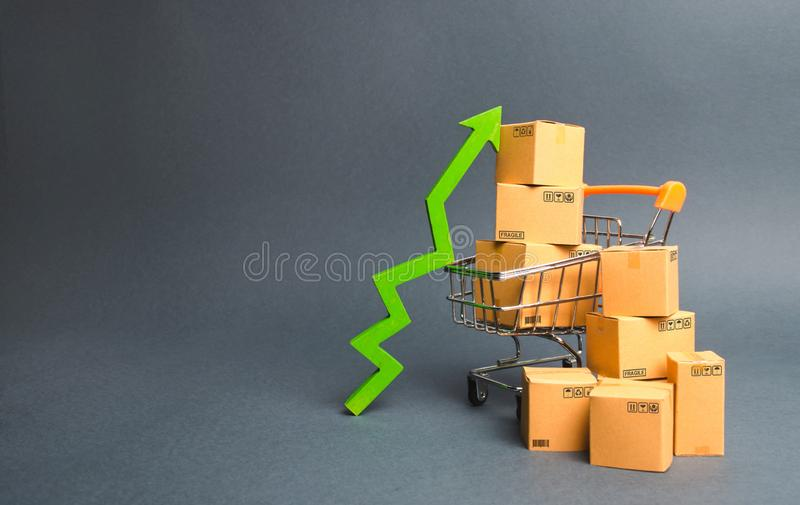 Shopping cart with cardboard boxes and a green up arrow. Increase the pace of sales and production of goods. Improving consumer sentiment, economic growth stock images