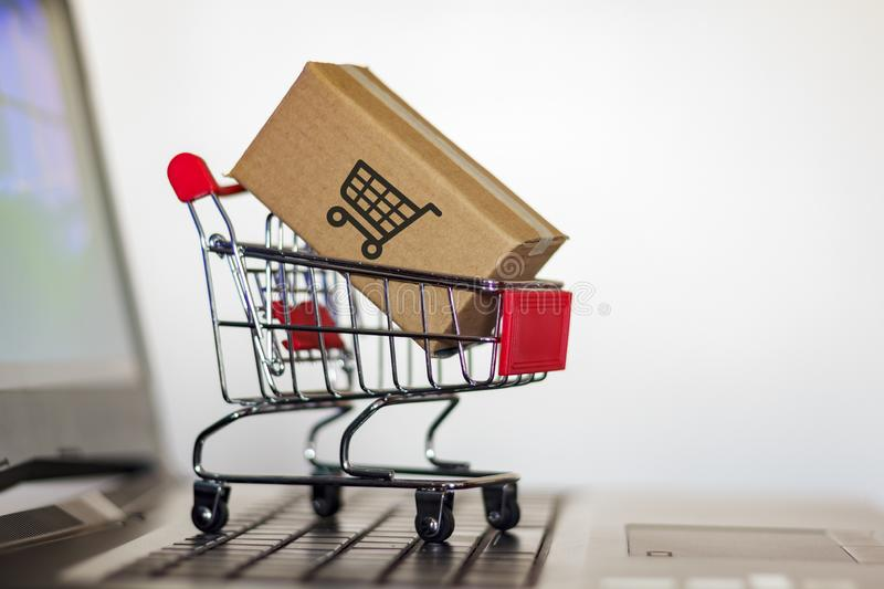 Shopping cart with Carton on computer keyboard. Online shopping, e-commerce and worldwide shipping concept royalty free stock photography