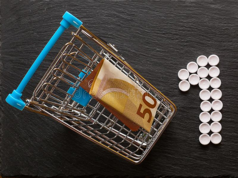 Shopping cart with cash money and number one made of pills, Concept care of your health is your priority. Top view stock photography