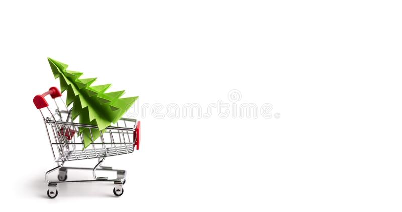 Shopping cart with Christmas tree inside on white royalty free stock photo