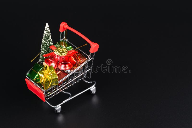 Shopping cart with christmas tree and miniature gift boxes on black background. Christmas and New Year shopping time background stock image