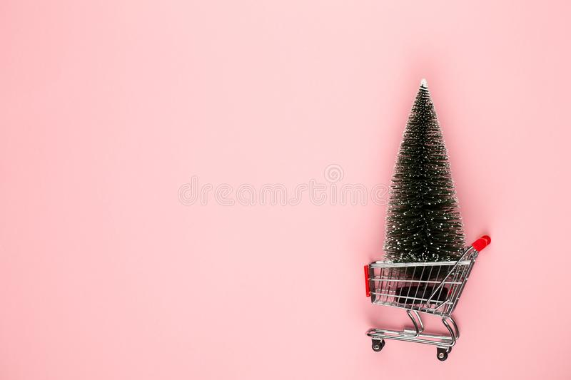 Shopping cart with christmas tree on red table stock photos