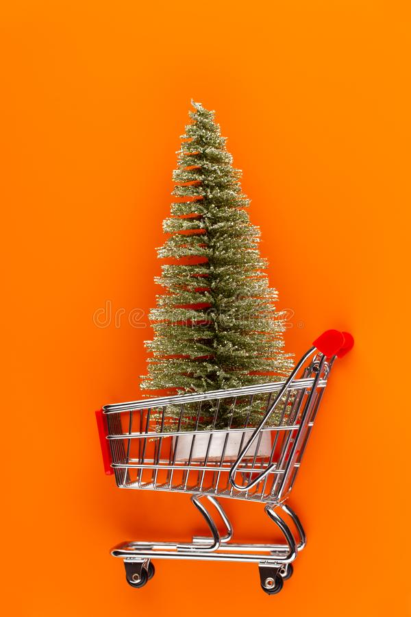 Shopping cart with christmas tree on red table royalty free stock images