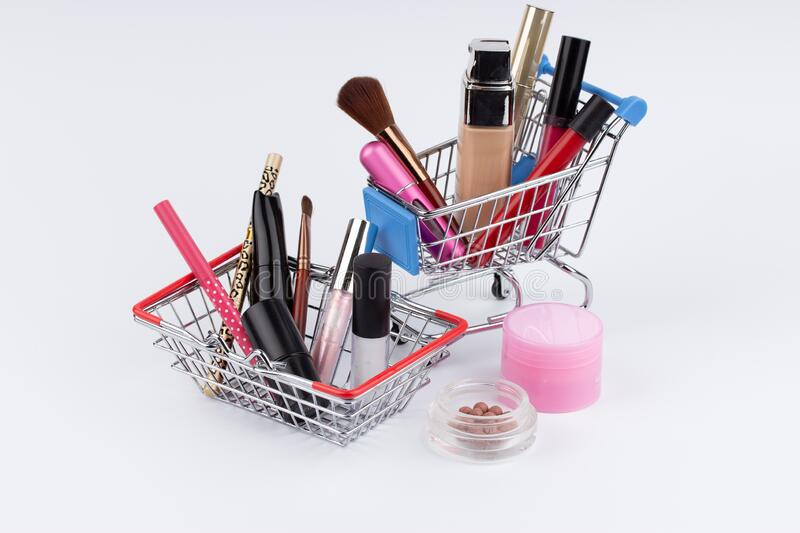 Shopping cart with cosmetics and moneys on white background.  royalty free stock photography