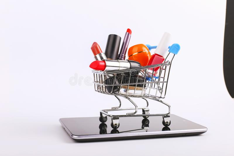 Shopping cart with cosmetics is on the smartphone. Online sales concept royalty free stock photos