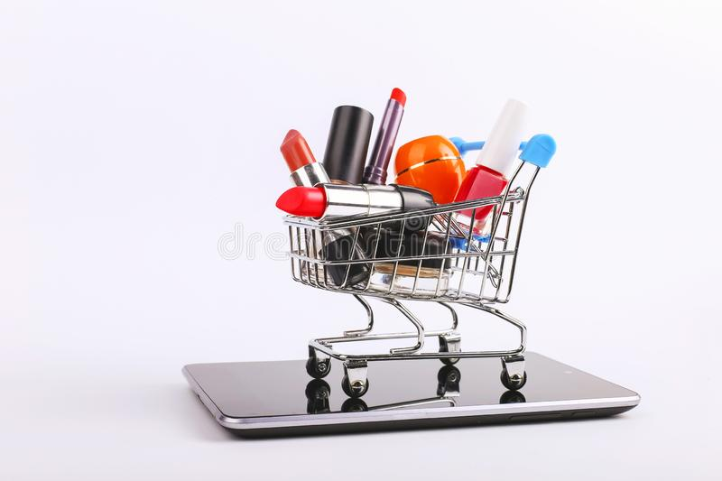 Shopping cart with cosmetics is on the smartphone. Online sales concept. Shopping cart with cosmetics is on the smartphone. Online sales, concept stock photography